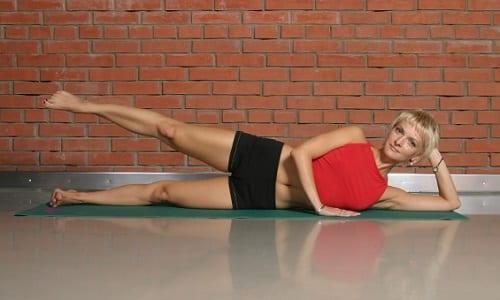 Одно из упражнений на боку: правая нога на вдохе поднимается, а на выдохе - медленно опускается