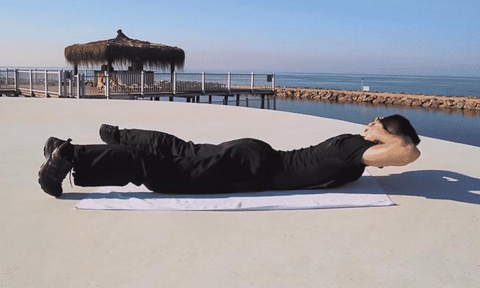 Упражнение №2 - лежа на животе, развести ноги в стороны, руки сложить за головой, максимально поднимать верхнюю часть тела, стараясь не отрывать ноги от пола